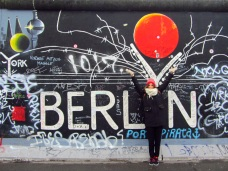 Pili in front of a graffiti on the wall, East Side Gallery, Berlin