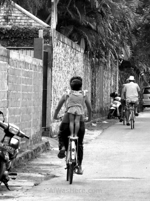 Balinese people and tourists cycling