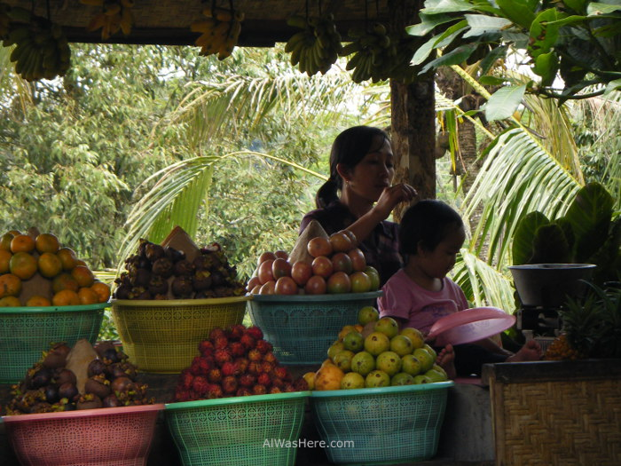 A lady removing her daughter'slice at her fruit stand