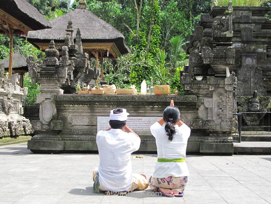 Peoplepraying in Tirta Empul facing an altar with several canang sari