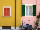 Motorcycle in front of colouful painted houses in gargnano, Italy