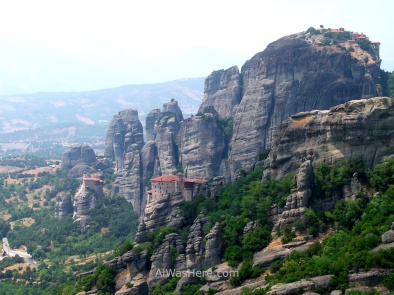 Three monasteries on rock boulders, on the left, in the center and in the upper right corner of the picture, Meteora